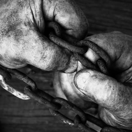 Male hands trying to free themselves from the chains on the wooden boards close up. Square black and white photo.