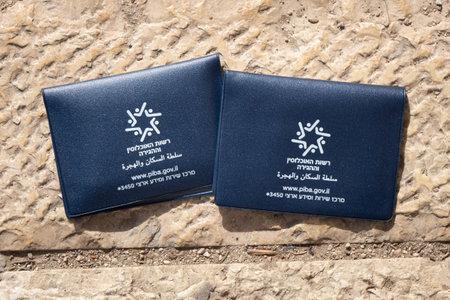 Jerusalem, ISRAEL - November 26, 2019. Temporary Israeli passports lying on the ancient stones in old Jerusalem. Translation of a writing: Population and Migration Board