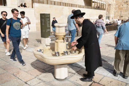 JERUSALEM, ISRAEL - November 26, 2019: Jewish orthodox man wearing a black traditional suit and a hat washing hands using a traditional ritual cup in old city near the Wailing wall in Jerusalem