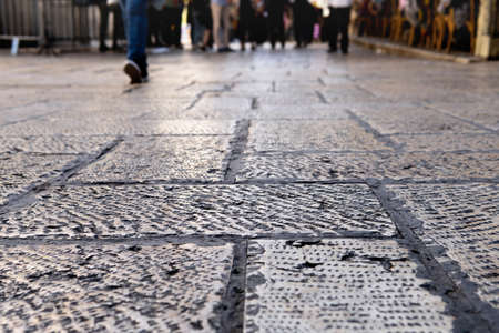 Ancient pavement stones on the old Jerusalem street close up with feet of walking people on the background