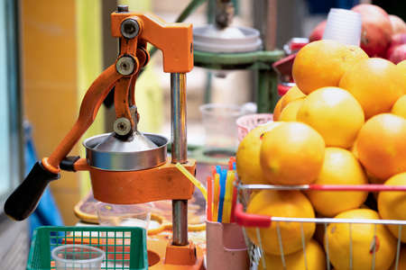 Juicer with a lot of ripe oranges outdoors on the street market in Jerusalem, Israel close up