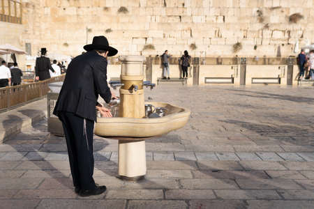 Jewish orthodox man wearing a black traditional suit and a hat washing hands using a traditional ritual cup in old city near the Wailing wall in Jerusalem Publikacyjne