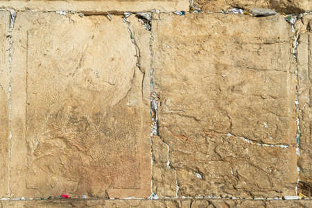 Fragment of the Wailing Wall with paper nortes with requests to god inserted into gaps between ancient stone plates