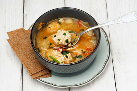 Bowl of a tasty hot soup with chicken meatballs and rye crispbreads on the white wooden boards Фото со стока