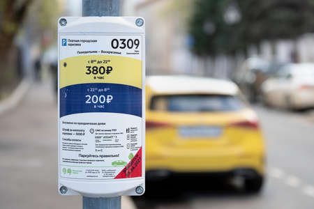 MOSCOW, RUSSIA - MAY 01, 2021: The sign of the expensive paid Parking zone in the center of Moscow with a blurred yellow taxi car on the background Publikacyjne