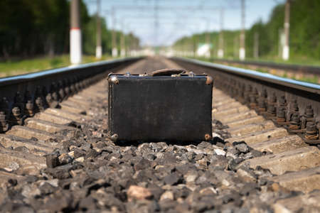 Old suitcase stands on the railways in summer morning