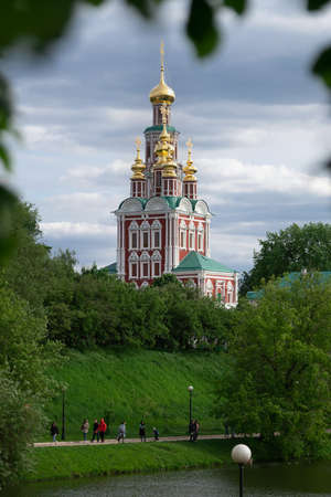 Moscow, Russia-May 30, 2021.View of the Moscow Novodevichy monastery with blurred tree leaves on the foreground