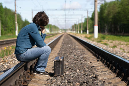 Woman with old suitcase sits on a rail of railroad and waits for a late train in summer morning