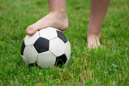Bare foot of a girl on the soccer ball in green grass Zdjęcie Seryjne