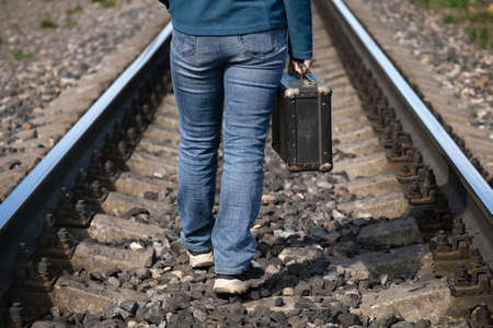 Woman with an old suitcase in her hand walks on sleepers of a railroad between rails
