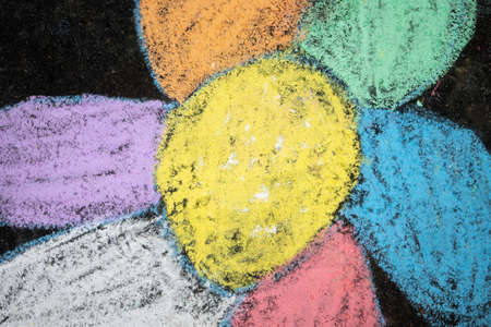 Childrens chalk drawing of a flower on the asphalt close up
