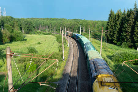 Above view of a long freight train moving along railway at countryside