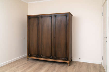 Old wooden brown wardrobe in a modern renovated living room with painted wallpaper