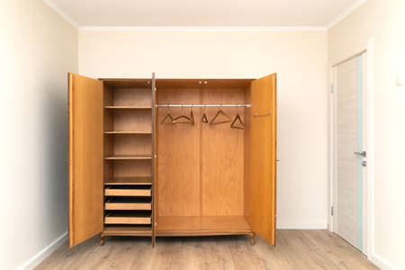 Old opened wooden brown wardrobe in a modern renovated living room with painted wallpaper Zdjęcie Seryjne