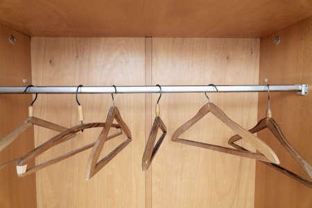 Wooden coat hangers hanging in old wardrobe