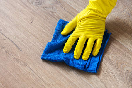 Hand in a rubber glove washing a laminate flooring with a wet cloth