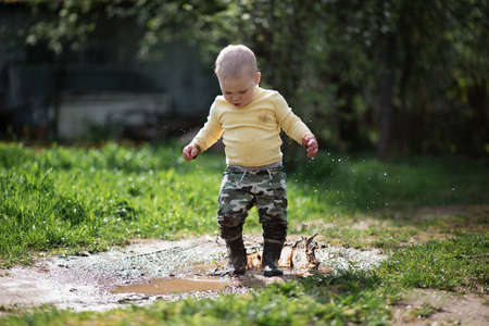 a little baby boy in rubber boots jumping and playing in the puddle