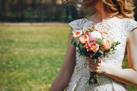 Bride in Wedding Dress with Wedding Bouquet in Hand in the Park