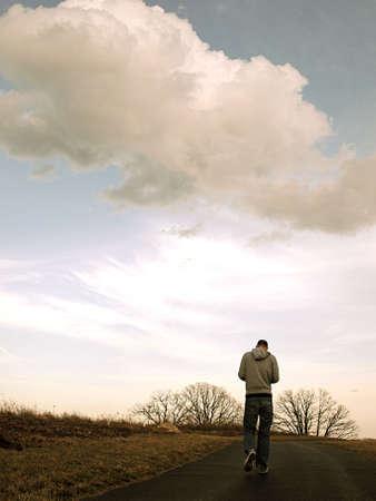 man walking under clouds photo