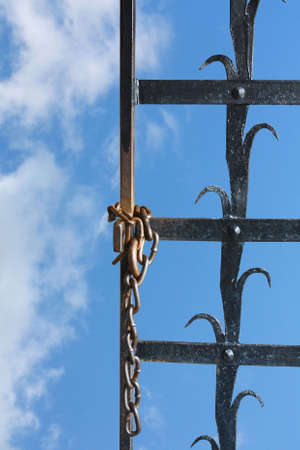 Iron grate with a chain on a background of the blue sky Stock Photo - 7985202