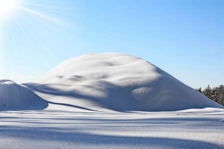 Winter landscape with snow-covered hill and clear blue sky Stock Photo