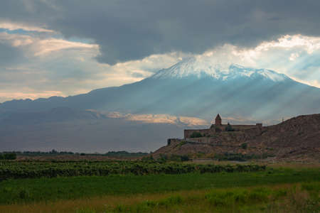 Khor Virap monastery on the background of mount Ararat. Sunset landscape with clouds and sunshine. Armenia.