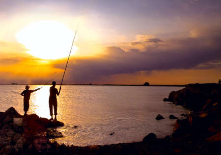 Beautiful  bright sunset at the sea coastline, two men fishing  photo