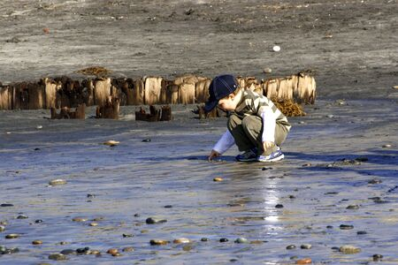 boy on the beach playing in the water. Stock Photo