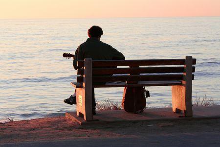 sunset. quiet evening. lone instrumentalist on the beach.