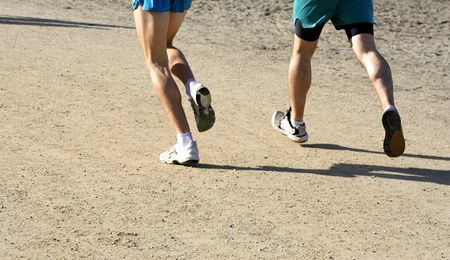 Sunny morning, close-up of mens legs running on the beach. Stock Photo