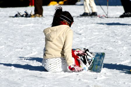 Girl with snowboard resting on the snow photo