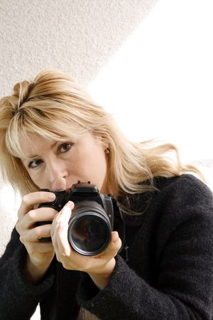Woman holding a digital camera. White background.
