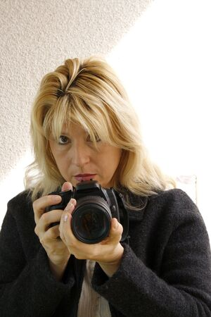 Woman holding a digital camera, ready for shoot. White background.