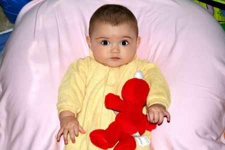Small happy baby girl with toy on the pink background Stock Photo