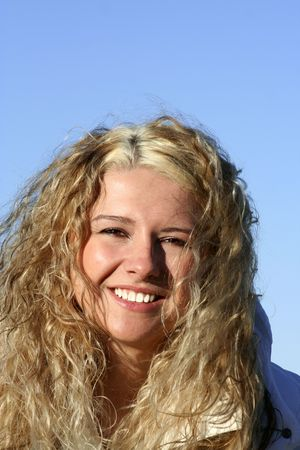 Happy smiling blond girl, blue sky
