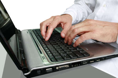 fingers on keypad of silver and black laptop Stock Photo
