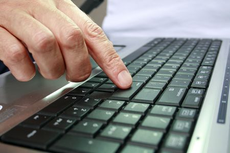 Fingers on keypad of silver and black laptop