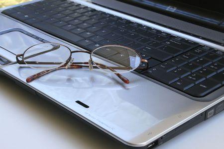Glasses lying on laptops keyboard.