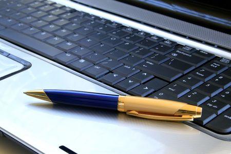 Pen lying on laptops keyboard.