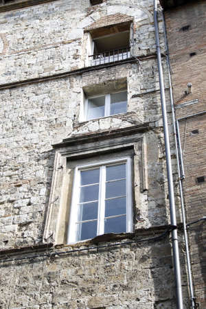 Old wall with windows in perspective. Siena , Italy