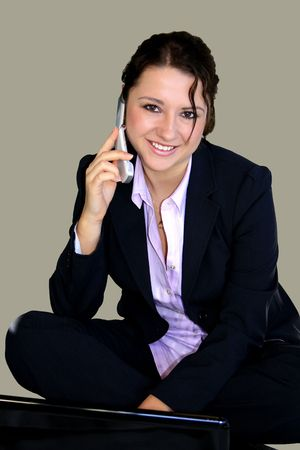 Beautiful smiling girl sitting on the floor with laptop and cell phone. photo