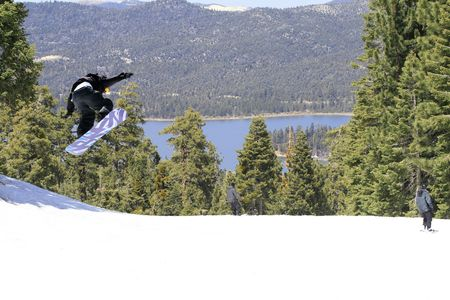 Winter. Lake view in Mountains. Snowboarder jumping high in the air Stock Photo