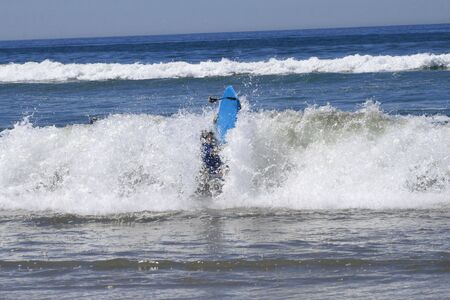 Summer time. Young boy with surf in waves Stock Photo