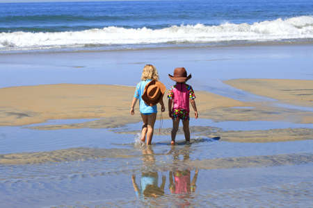 Two children are walking at the beach by the water