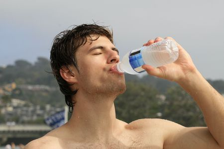 Thirsty man drinking water from water bottle on the beach