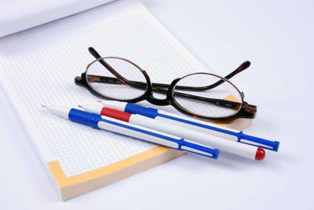 Glasses and pens on a notebook