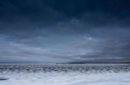 A severe winter evening and a lake covered with ice and snow