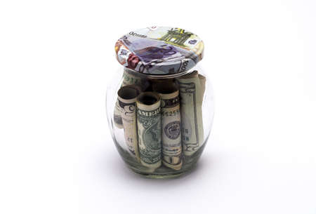 A glass jar with a lid in which a lot of American dollar bills Stock Photo
