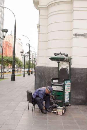 LIMA, PERU - AUG 29TH 2015: Man dedicated to the informal economy in the streets of downtown Lima, is dedicated to polishing shoes for people