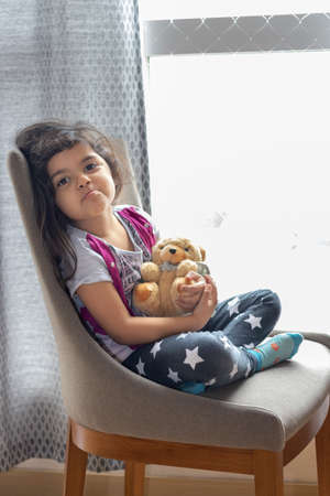 Cute little girl playing with her teddy bear
